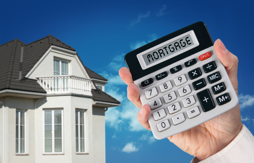 a mans hand holding a mortgage calculator with the word mortgage in the calculator window against a background of a blue sky and partial house front - home mortgage tips