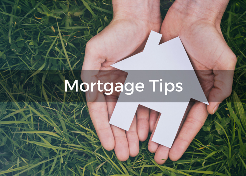 Two outstretched hands holding a cut out of a house with a mortgage tips banner laying across it - Home Mortgage Tips