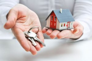two outstretched hands, one holding a set of keys and the other a small model house - home mortgage tips