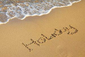 holiday written in the sand at the sea shore
