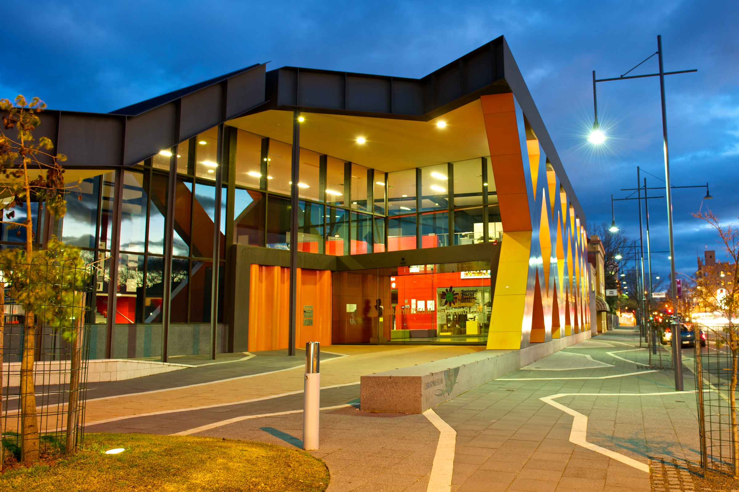 photo of a modern library building lit up at early evening